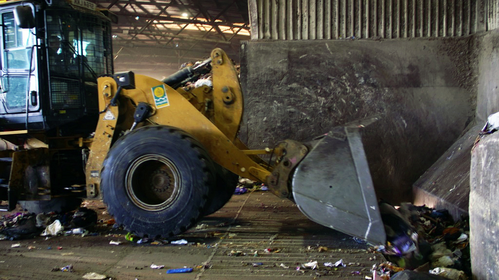 A bulldozer scoops up waste in a warehouse