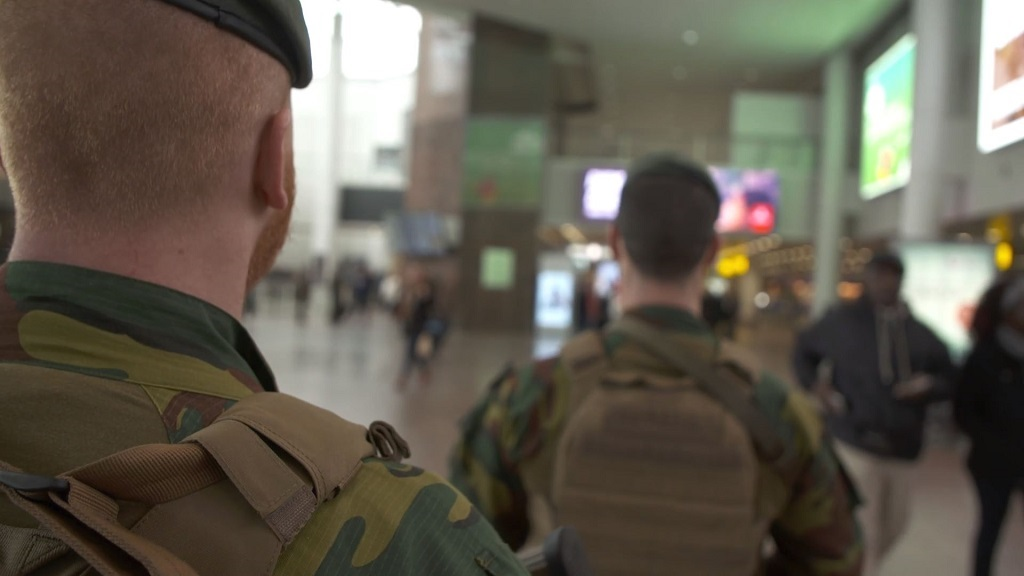 Armed soldiers walk through an airport